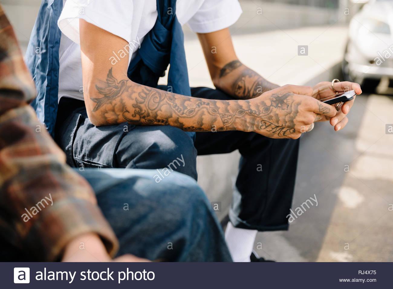Latinx joven con tatuajes en los brazos texto con teléfonos inteligentes. Imagen De Stock