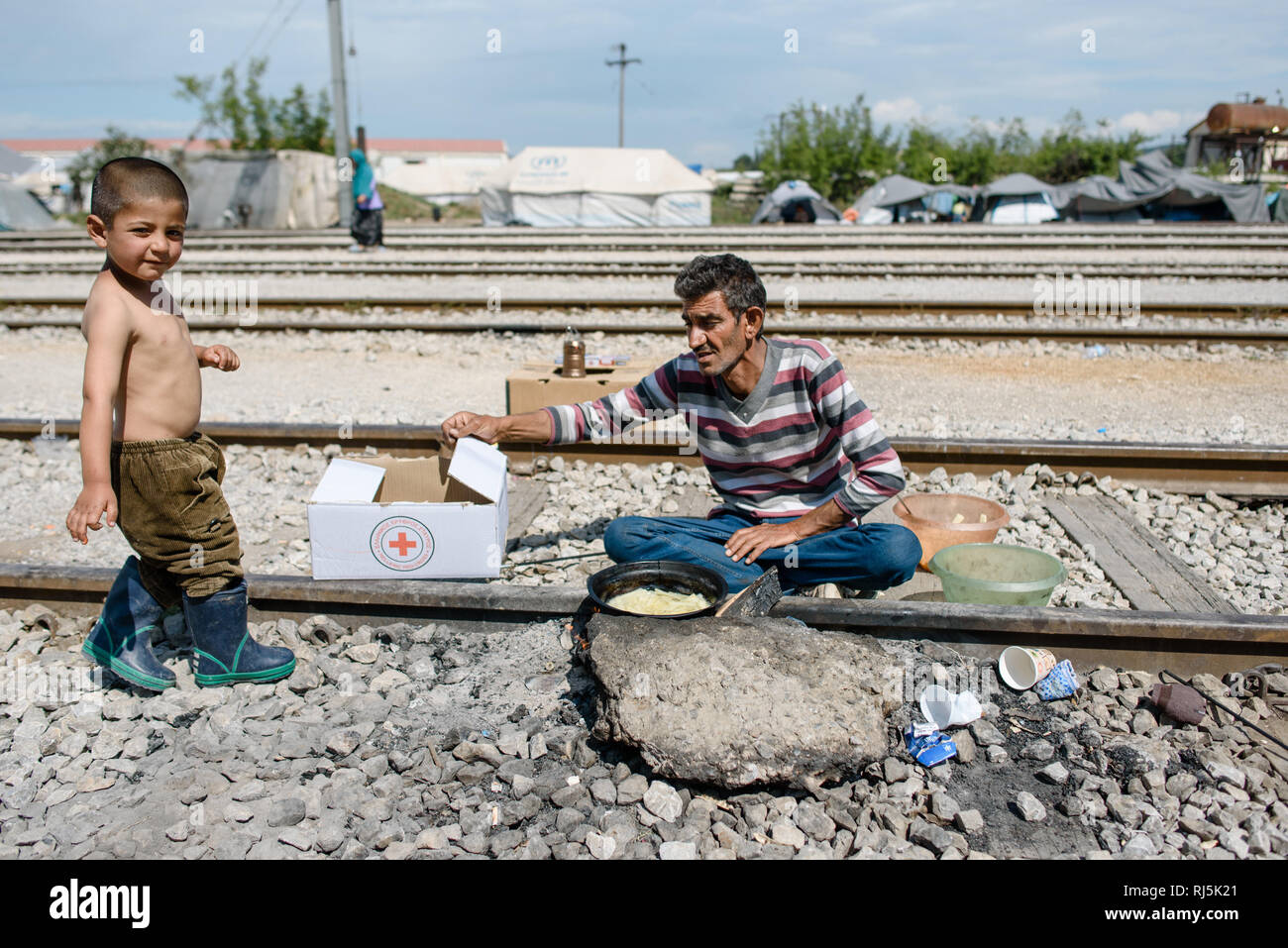 Ein Vater kocht für sich und seinen Sohn ein Mahlzeit auf den Zuggleisen. Von Idomeni Flüchtlingscamp en Griechenland an der Grenze nach Mazedonien, Foto de stock
