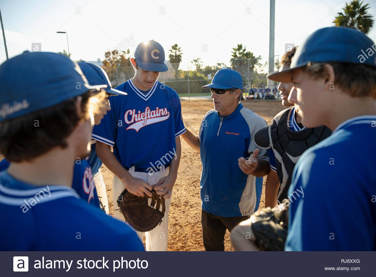 El entrenador y los jugadores de béisbol en se apiñan en campo soleado Imagen De Stock