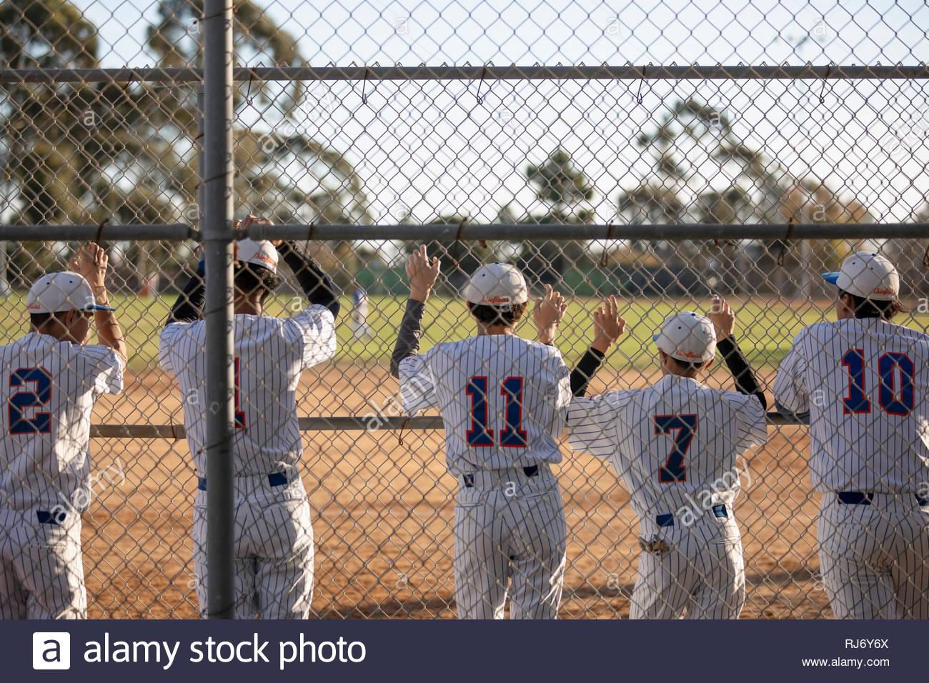 Equipo de béisbol viendo juego detrás de valla Imagen De Stock