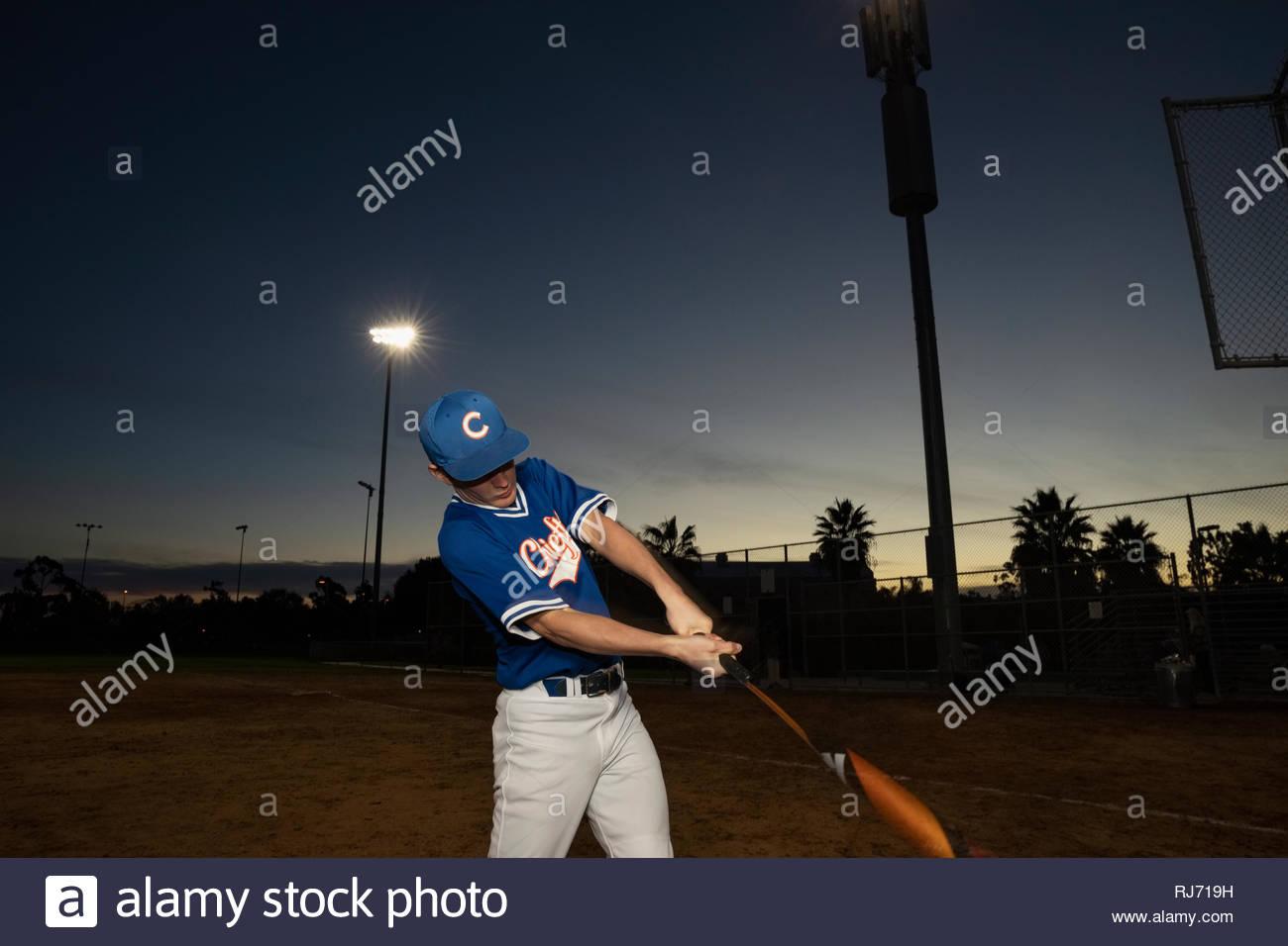 Jugador de béisbol con bat practicando swing en el campo de noche Imagen De Stock