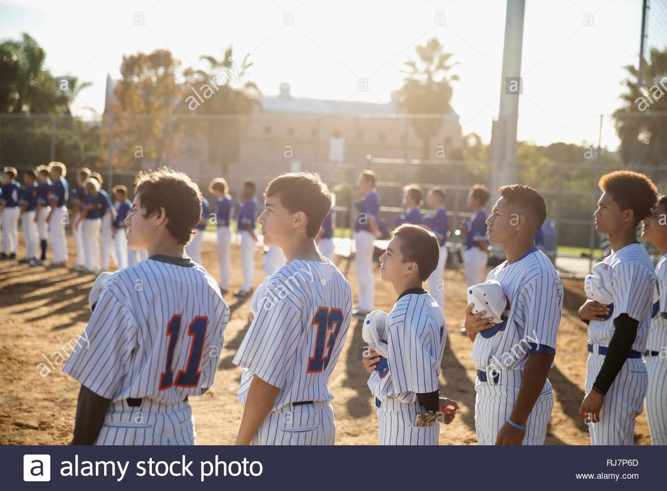 Los jugadores de béisbol de pie en una fila para el himno nacional en el campo soleado Imagen De Stock