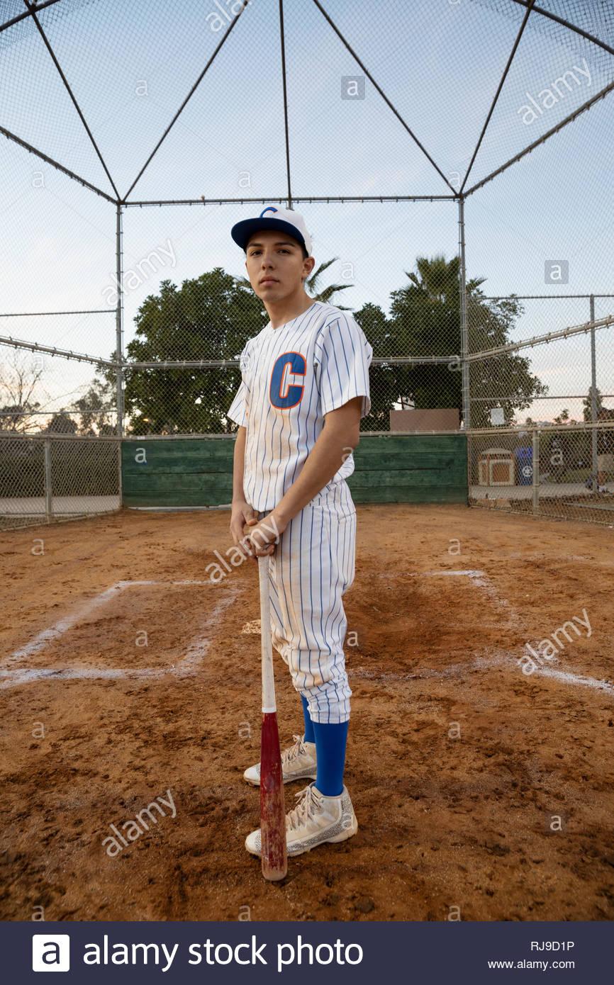 Retrato seguros, decididos Latinx jugador de béisbol con bat en el campo Imagen De Stock