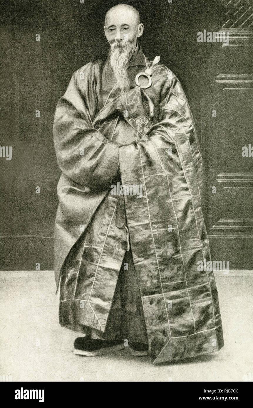 Sacerdote budista en su túnica de oficina, China. Está hecha de tela roja cosida con algodón blanco, para simbolizar los trapos de la pobreza. Foto de stock