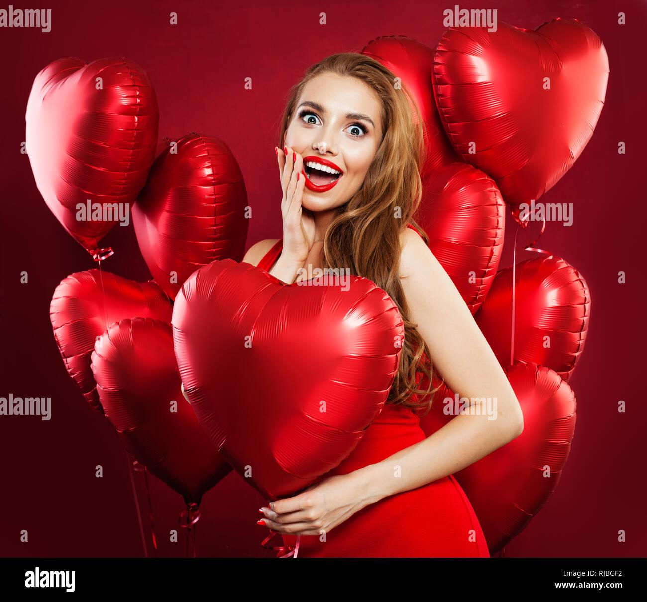 Sorprendido Mujer Sosteniendo Globos Corazón Rojo Retrato