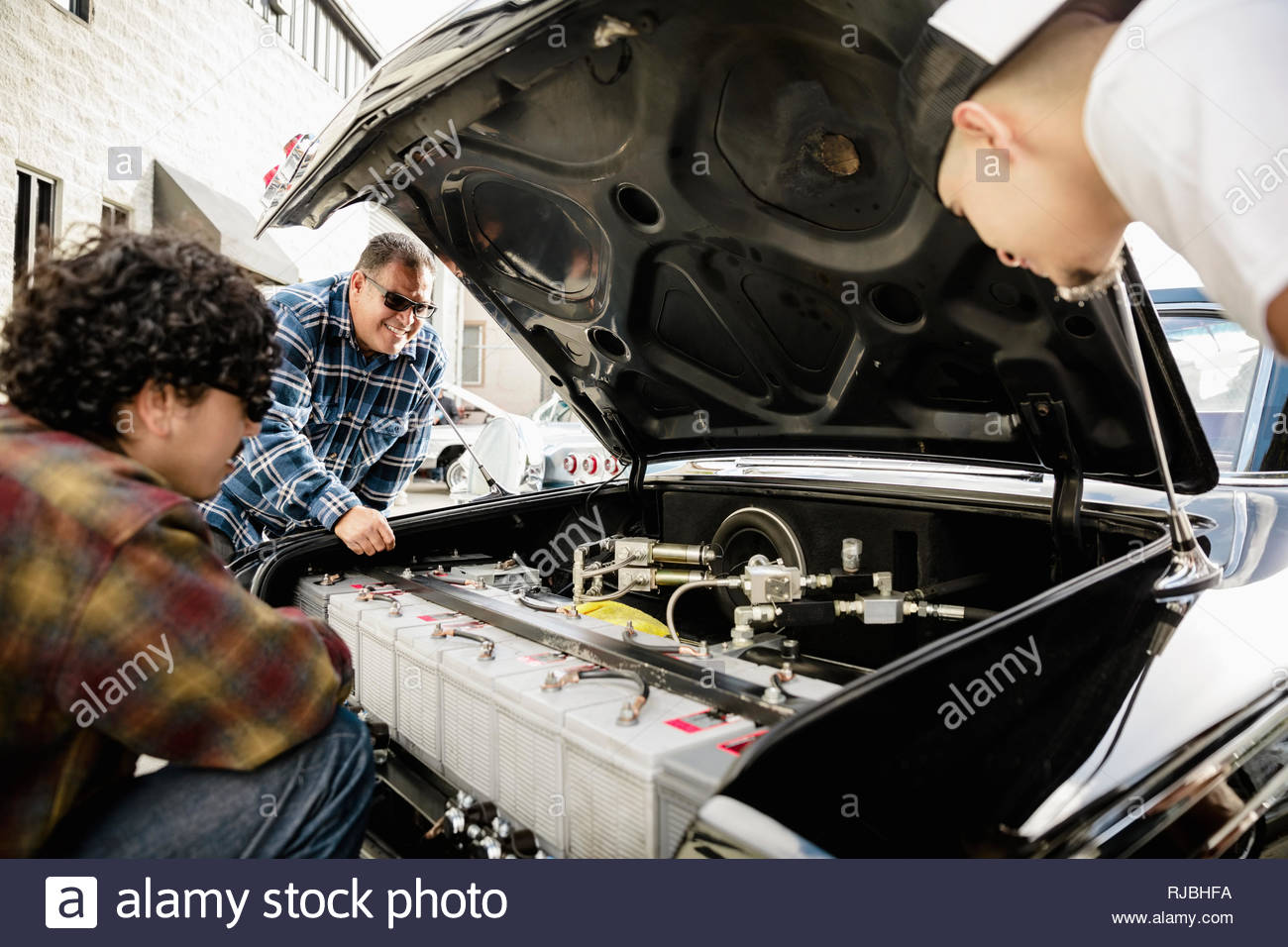 Amigos hombres Latinx desproteger el sistema hidráulico de baja rider car Imagen De Stock