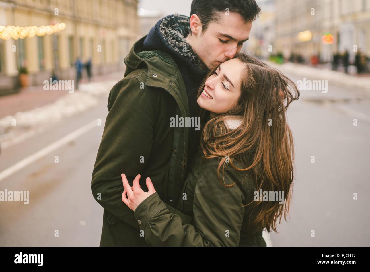 Tema el amor y el romance. Los jóvenes caucásicos pareja heterosexual en el amor estudiantes novio chica abrazos y besos en el centro de la carretera en el centro de Foto de stock