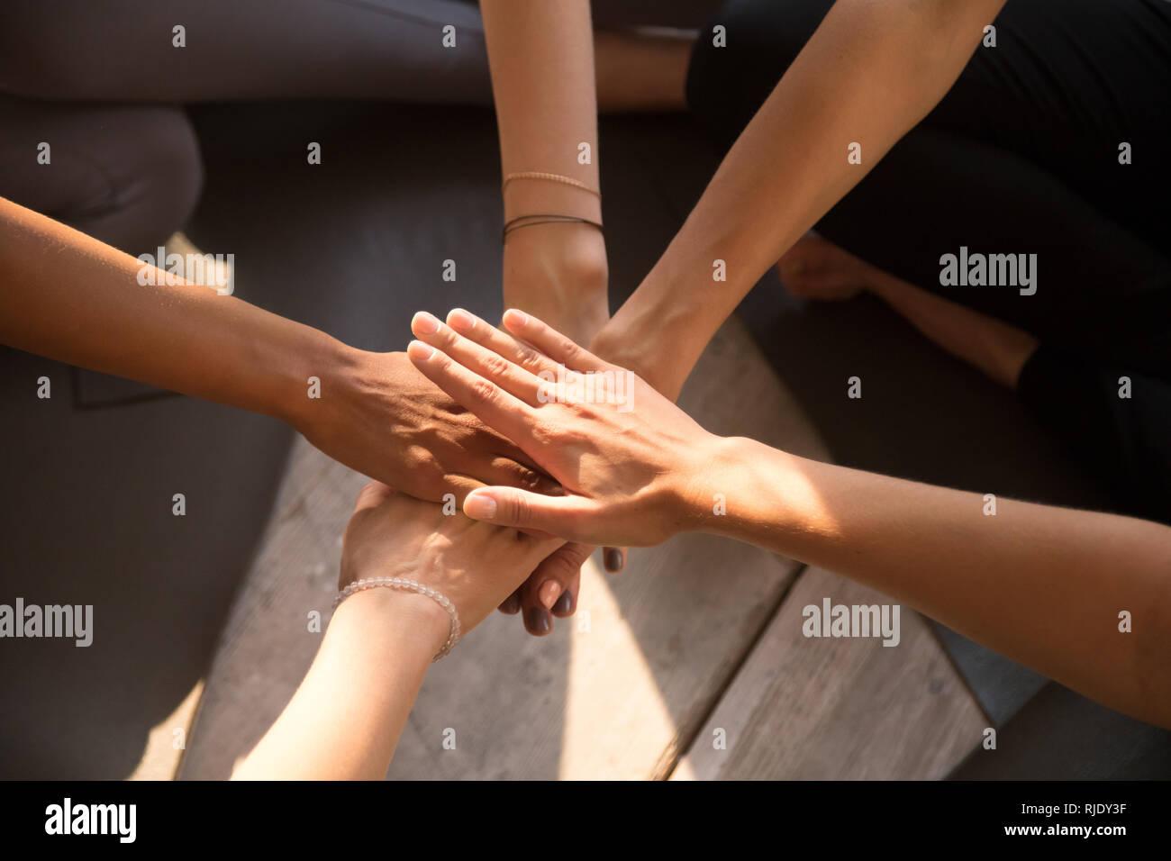 Vista superior de la pila de mujeres manos comprometidas en actividades de teambuilding Imagen De Stock