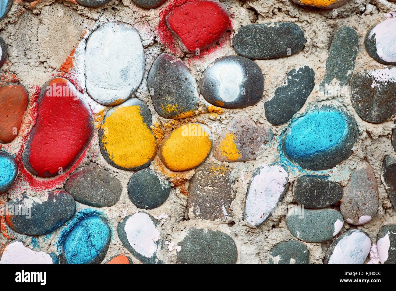 Colorido adoquines sobre la superficie con textura áspera de un muro de piedra de guijarro Imagen De Stock