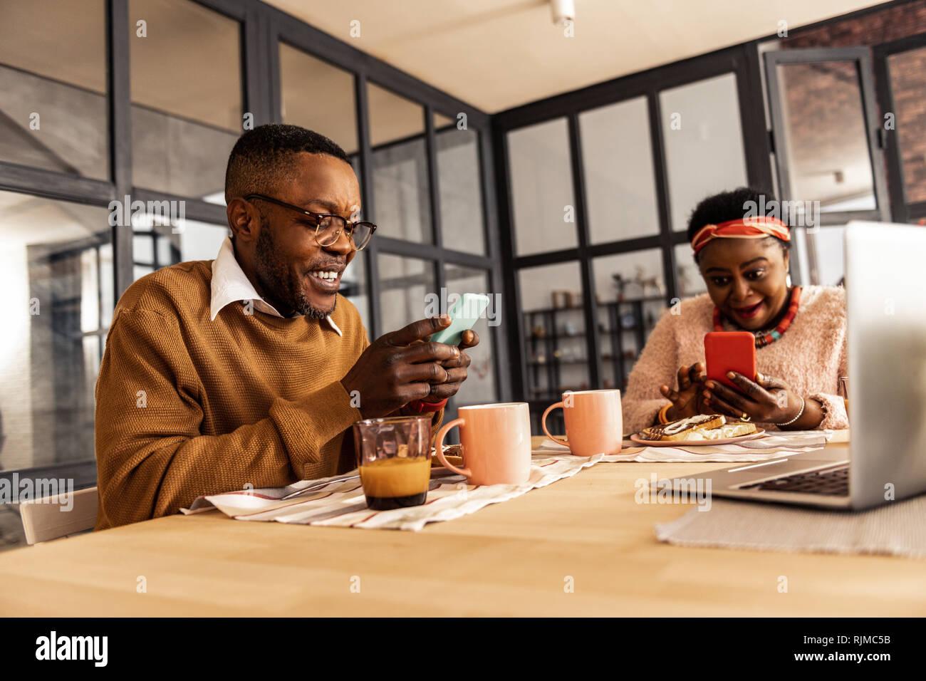 Encantado gozoso par que participan en sus smartphones Foto de stock