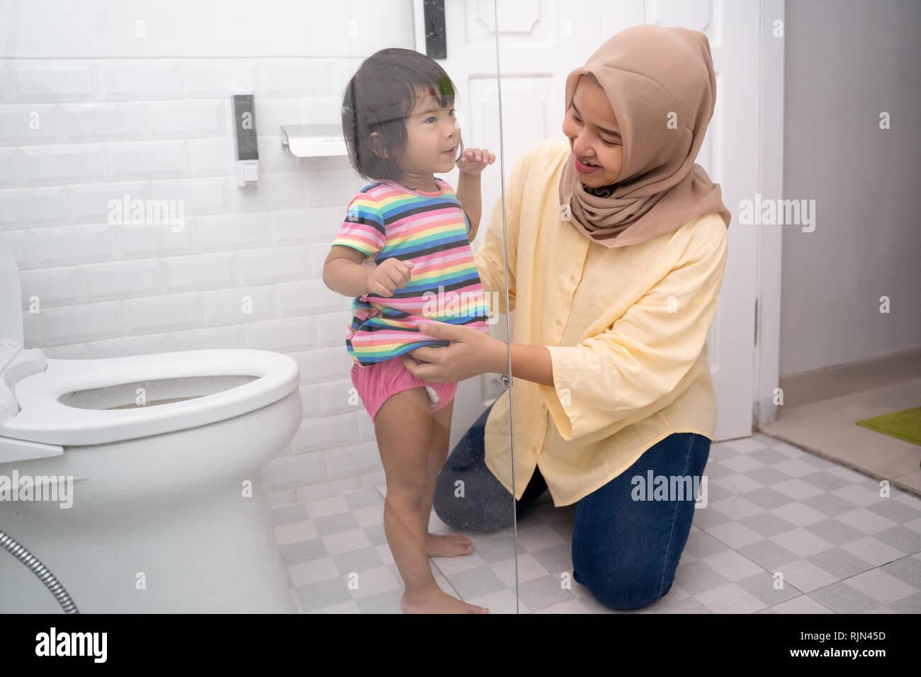 Madre musulmán ayudar a su niño a usar wc Foto de stock