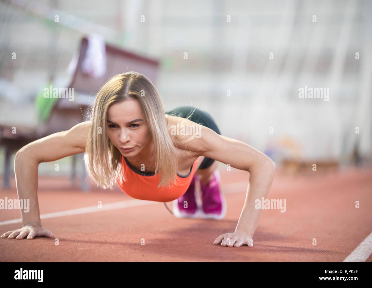 Colocar joven mujer atlética hacer empuje ups Foto de stock