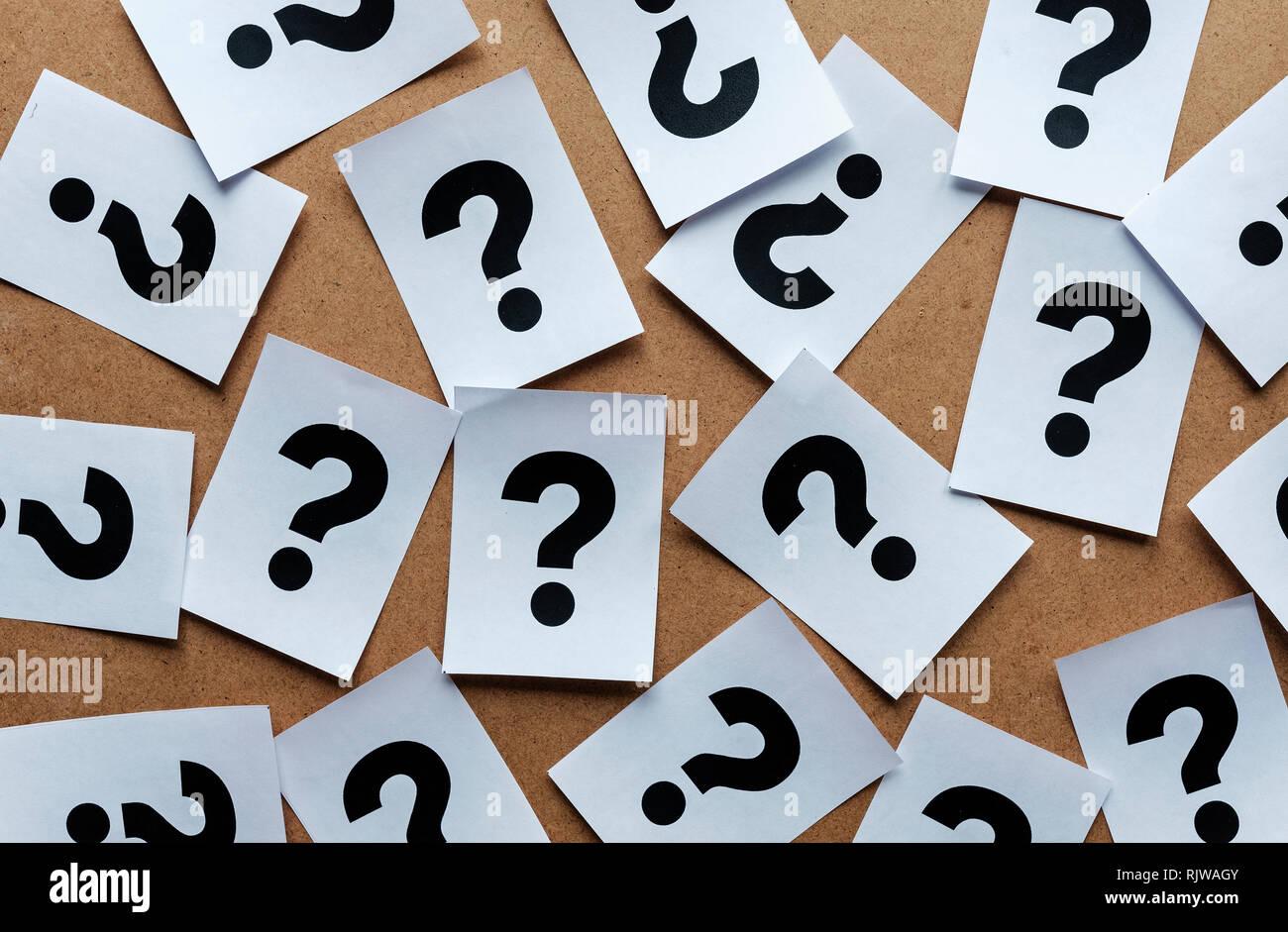 Los signos de interrogación en tarjetas de papel dispersos al azar sobre un fondo de madera en una imagen conceptual Foto de stock