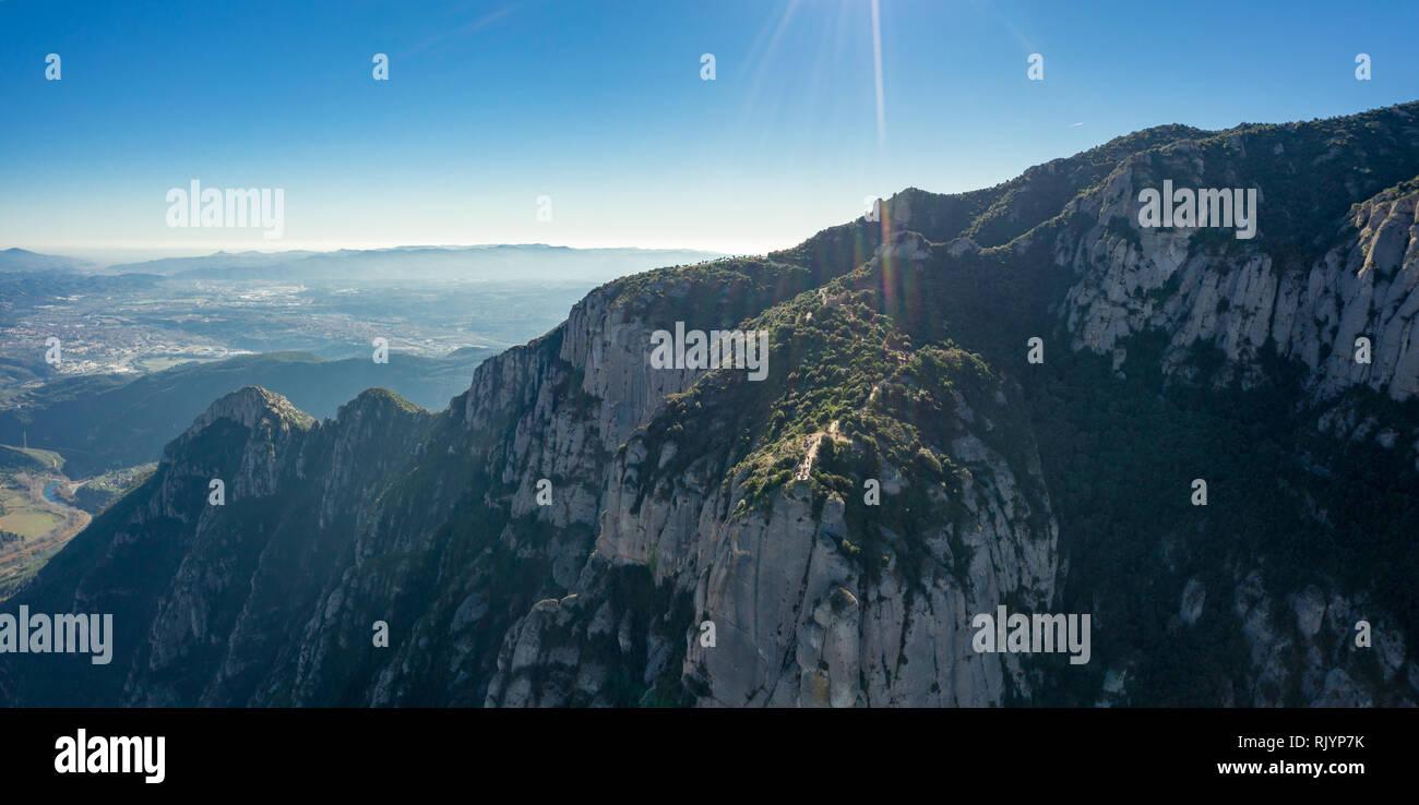 Vista aérea; zumbido de multi-culminó cordillera cerca de Barcelona; invierno soleado día despejado y horizonte azul; erupción del volcán provocó la emer Foto de stock