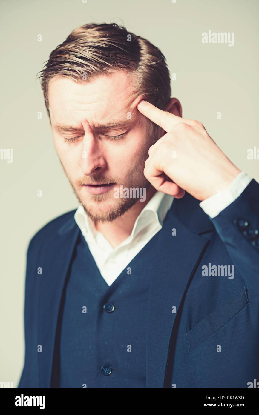 Joven intelectual con los ojos cerrados tratando con problemas con el retrato del hombre de negocios cansados presionando su dedo índice en la cabeza aislada sobre gris Foto de stock