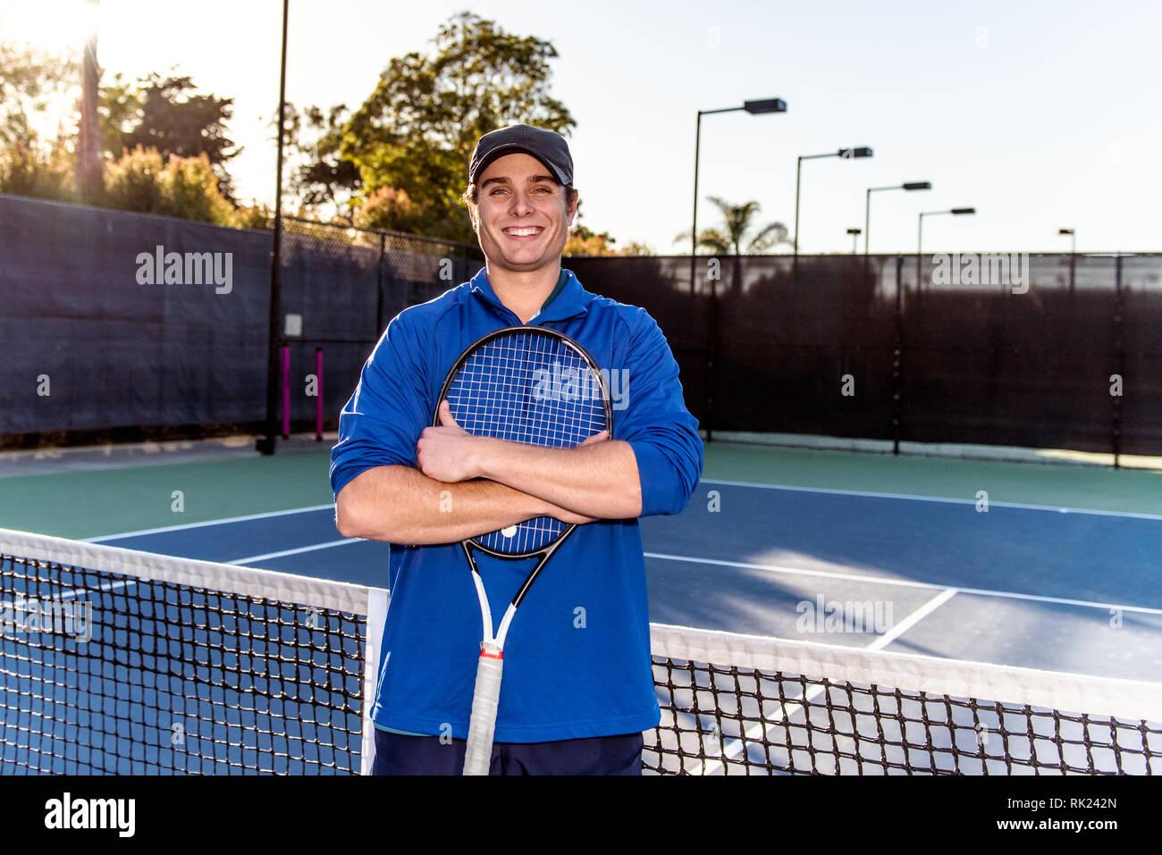 Joven y de buena apariencia de tenis profesional docente mostrando la sonrisa y la expresión feliz en la cancha de tenis. Foto de stock