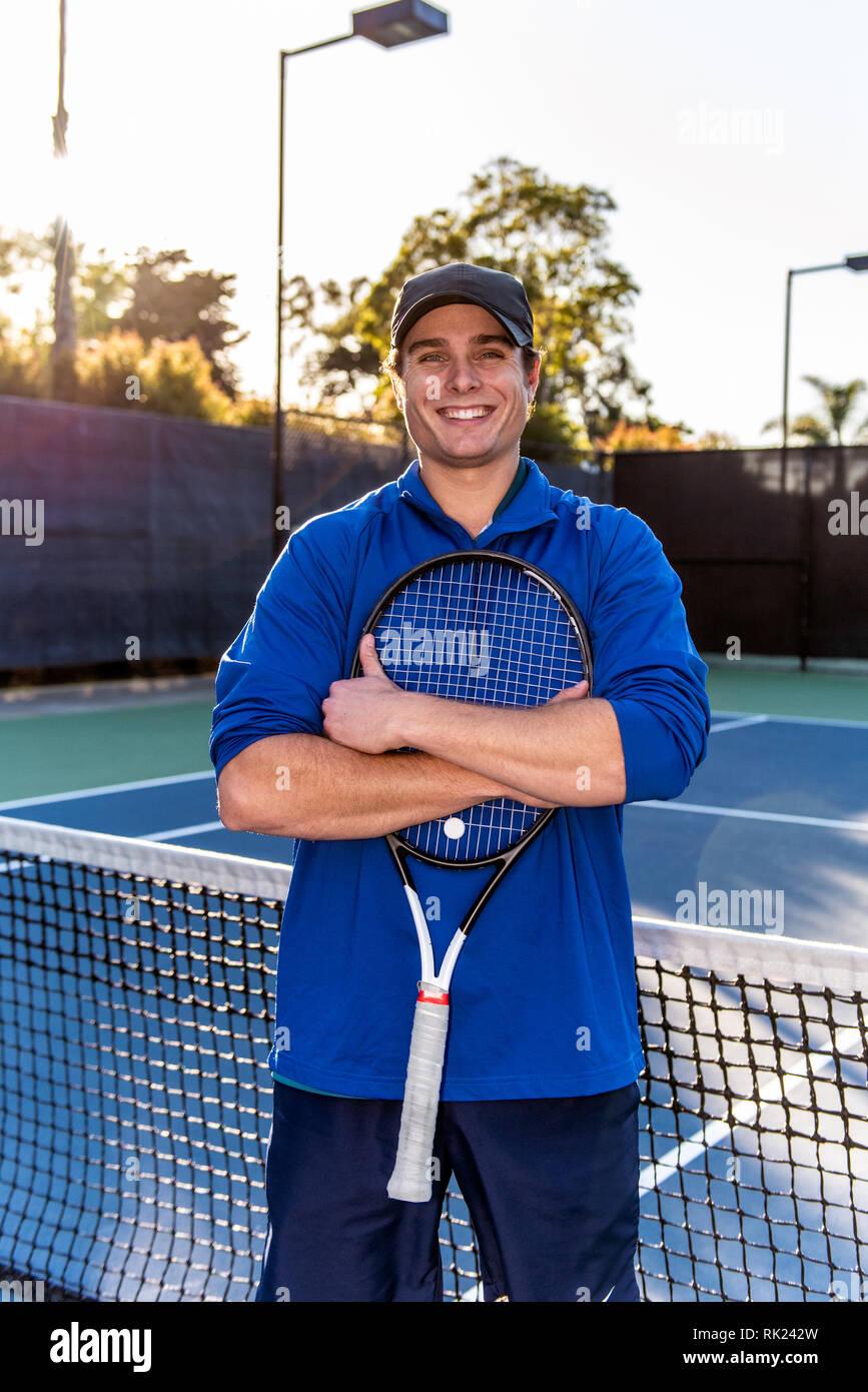 Cerrar vista de jóvenes y de buena apariencia de tenis profesional docente mostrando la sonrisa y la expresión feliz en la cancha de tenis. Foto de stock
