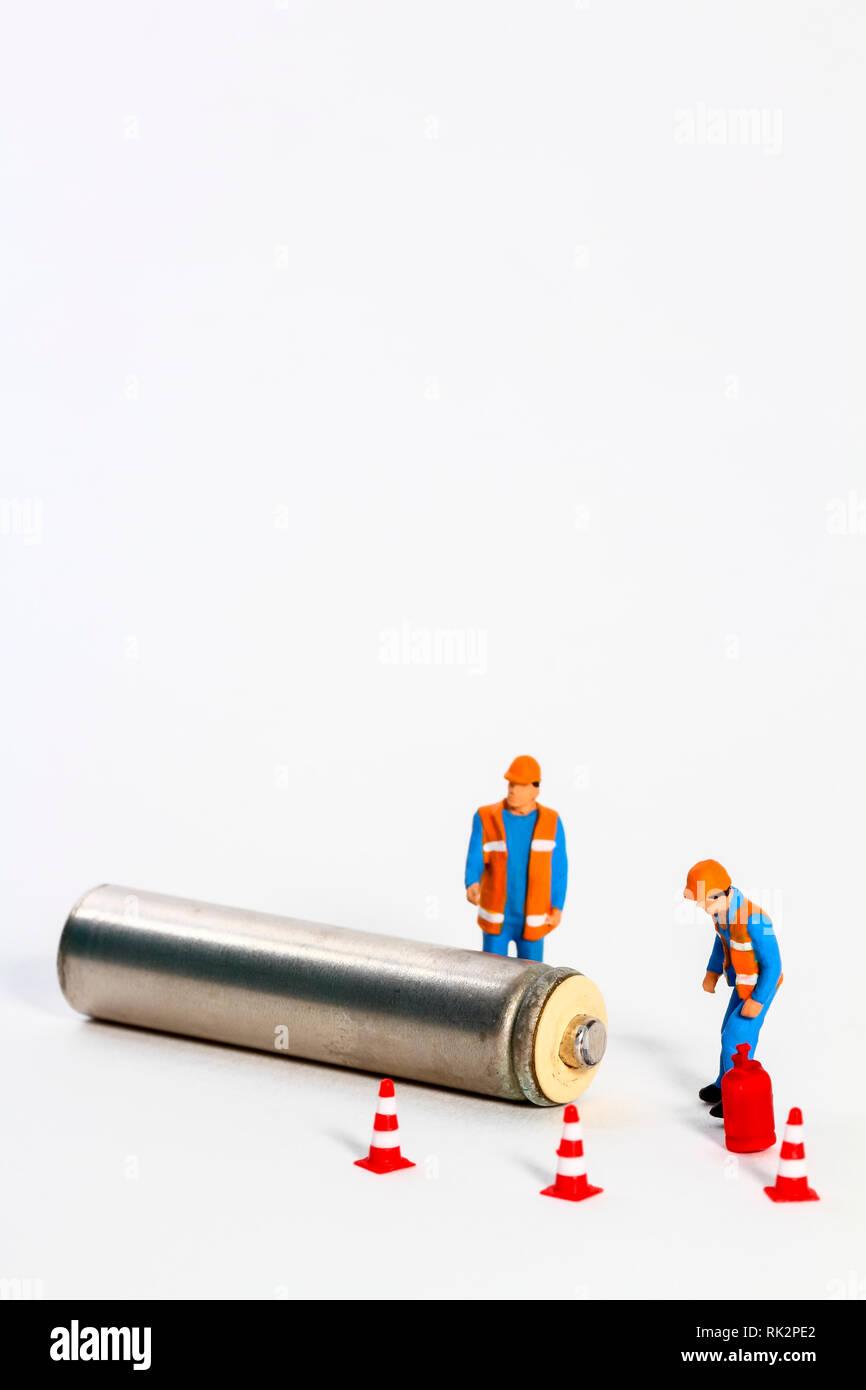 Diorama imagen conceptual de la gestión de residuos que consta de miniture figura obreros mirando una batería Imagen De Stock