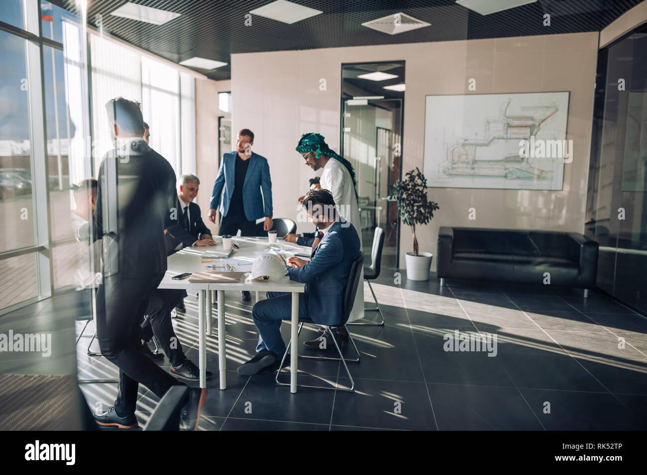 Grupo multiétnico de socios de negocios de diversas edades y etnias se reunieron para la reunión para discutir los detalles de la expansión de las empresas hacia el este - vie Foto de stock