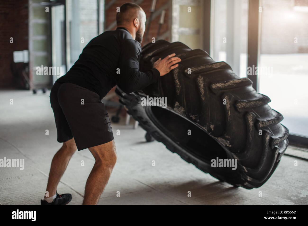 CrossFit técnica del neumático. Potente culturista demuestra las reglas y el fin de la formación con los improvisados powerlifting elemento en fitness club. Foto de stock