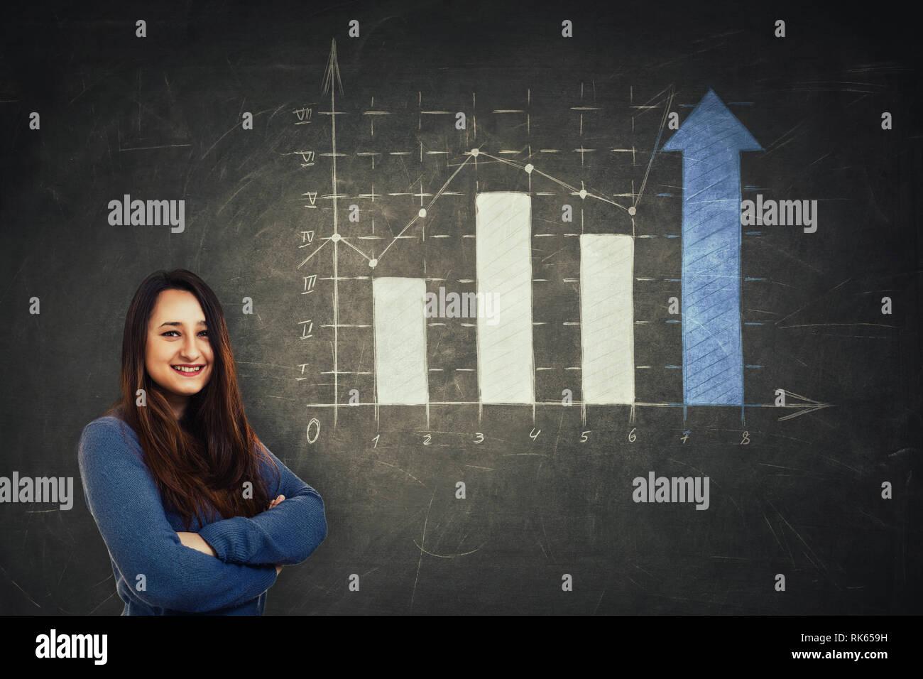 Pretty Woman holding analista de brazos cruzados frente a una enorme pizarra con dibuja un gráfico de creciente con las flechas hacia arriba. Industrias comerciales beneficios Foto de stock