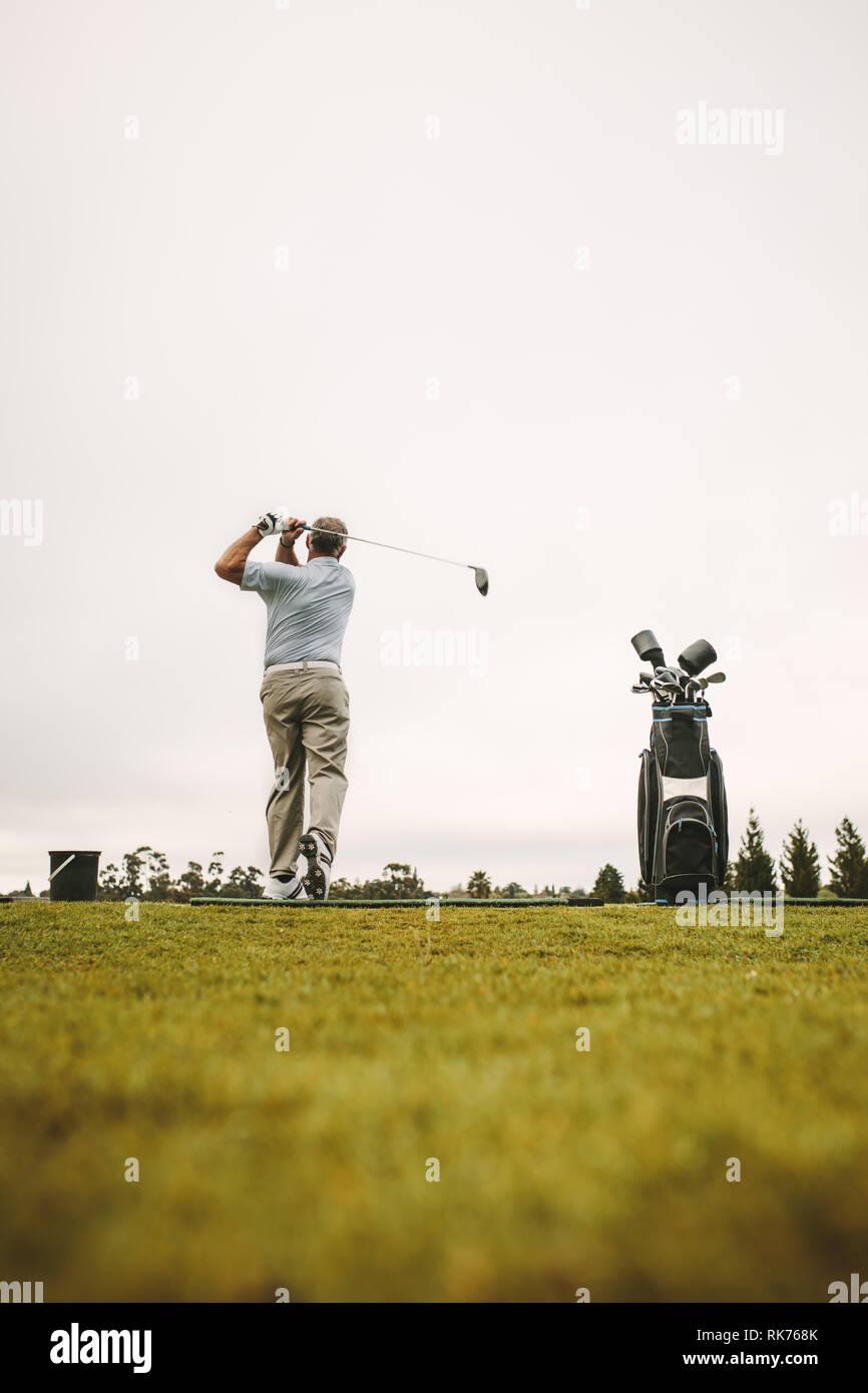 Hombre Senior practicando sus tiros en el driving range. La longitud total del golfista masculino senior de practicar en el campo de golf. Foto de stock