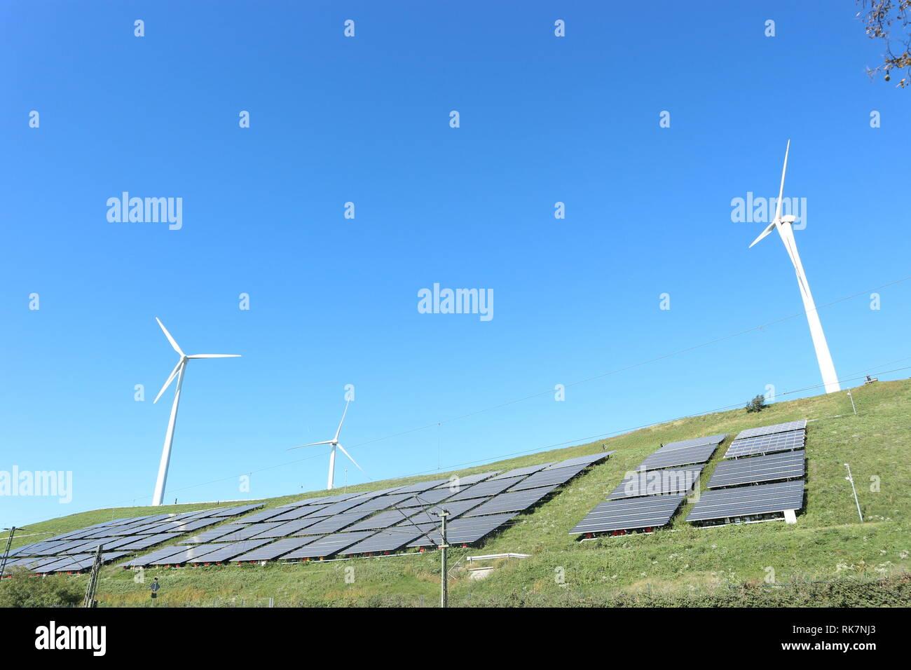 Celda del relleno sanitario restaurado con células fotovoltaicas y aerogenerador Imagen De Stock