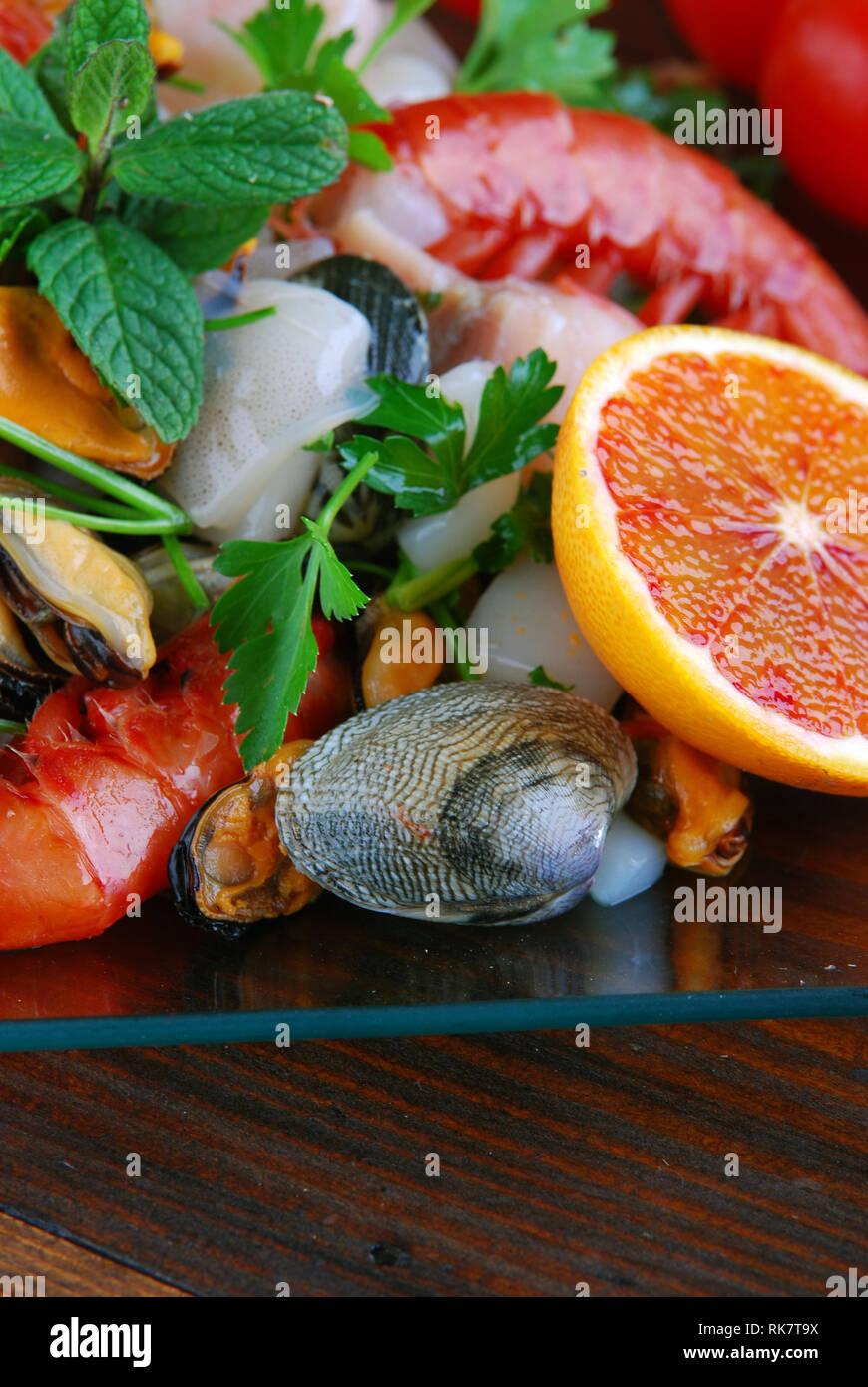 Cristal platos con pescado, moluscos y mariscos crudos de bonito en la plancha de madera Foto de stock
