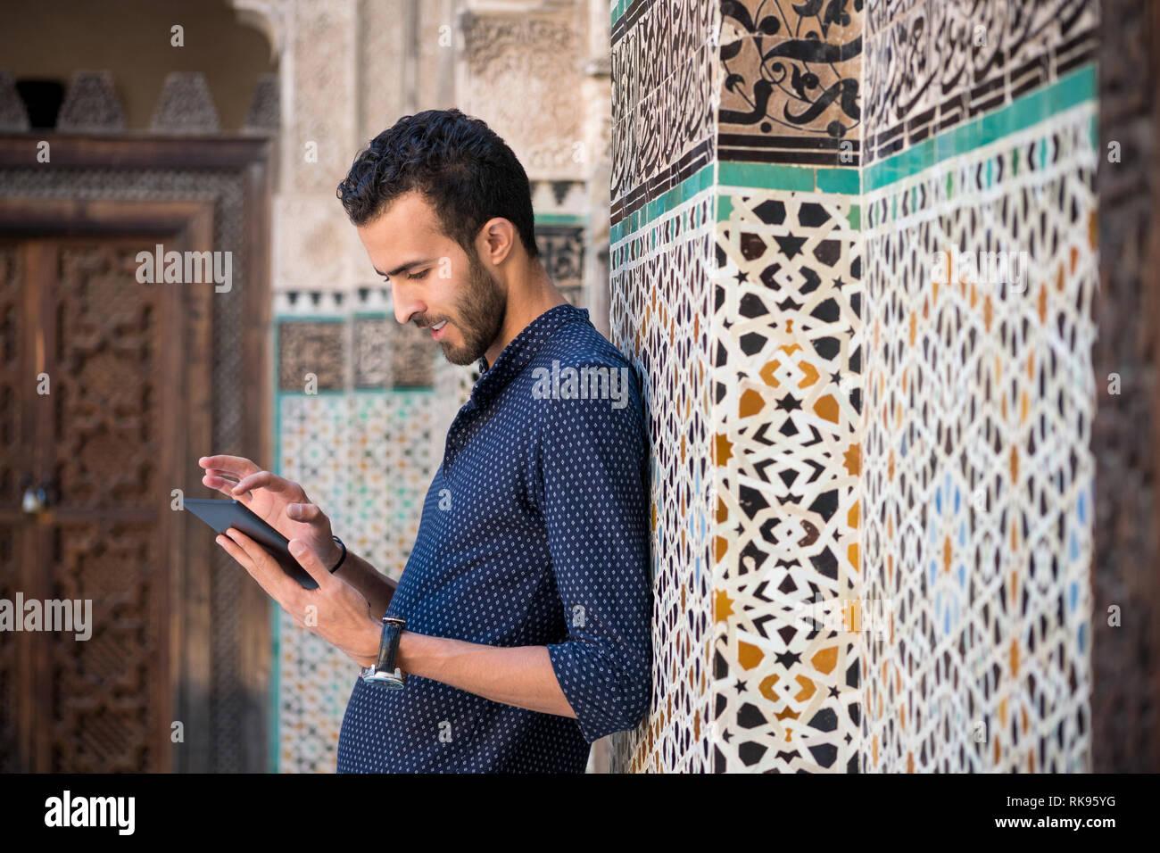 Joven musulmلn en ropa casual y sonriente trabaja en Tablet en ambiente árabe tradicional Imagen De Stock