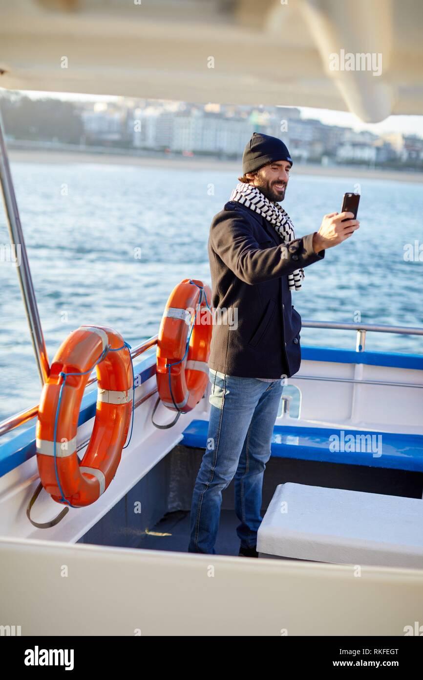 Un hombre adulto en un viaje en barco a la Isla Santa Clara, La Bahía de La Concha, Donostia, San Sebastián, Gipuzkoa, País Vasco, España, Europa, Invierno Imagen De Stock