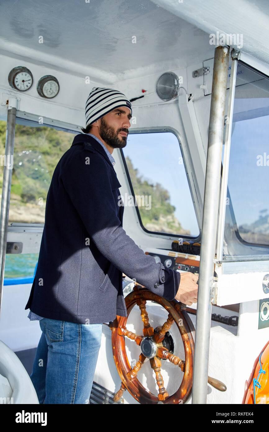 Marinero, un hombre adulto con el timón en un viaje en barco a la Isla Santa Clara, Donostia, San Sebastián, Gipuzkoa, País Vasco, España, Europa Imagen De Stock