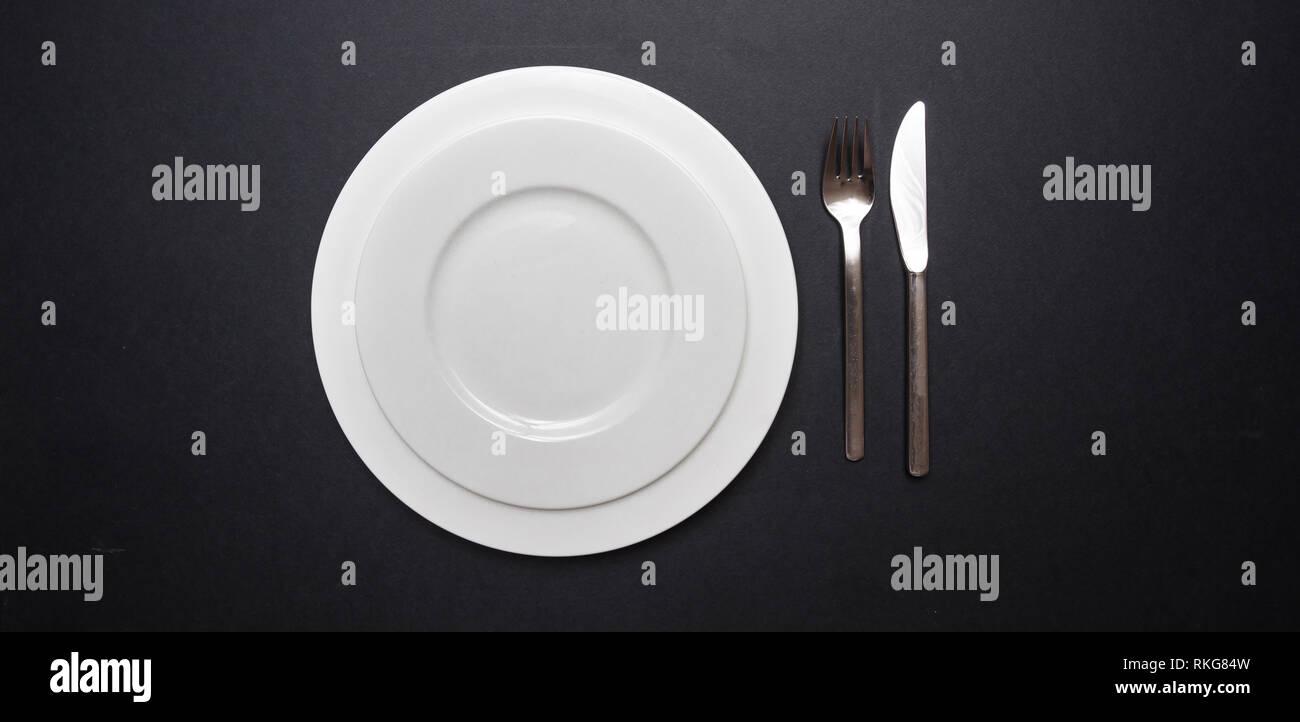 Coloque la tabla de ajuste de color negro. Conjunto de platos y cubiertos de blanco en blanco sobre fondo de color negro, vista superior, espacio de copia Foto de stock