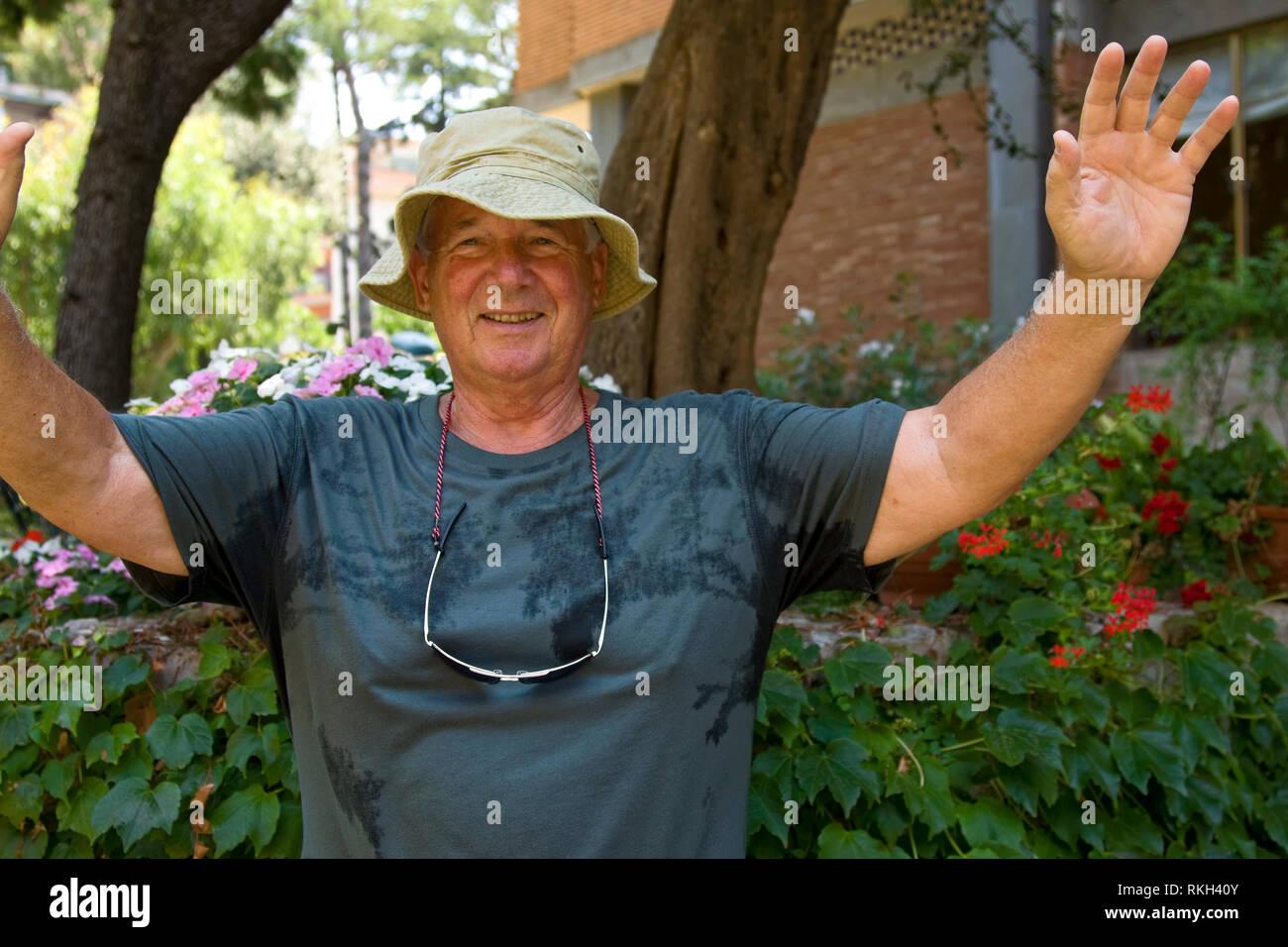 Hombre, brazos levantados mostrando CAMISETA MOJADA; transpiración; sombrero, anteojos de sol, calor; el calor; sonriente, feliz verano; señor; horizontal Imagen De Stock