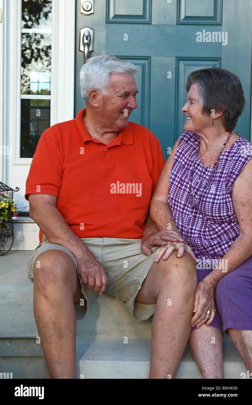 Las parejas ancianas sentadas en pasos, fuera de la casa; habla; sonriente, feliz, compañeros, familia, verano; señor; vertical Imagen De Stock