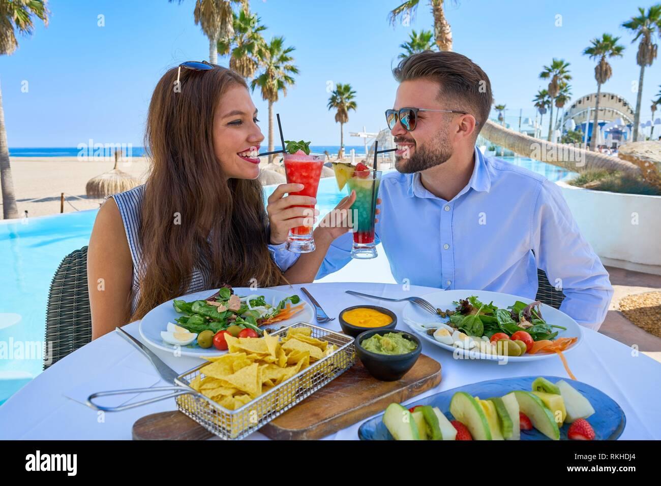 Pareja joven con cócteles en el restaurante de la piscina. Imagen De Stock