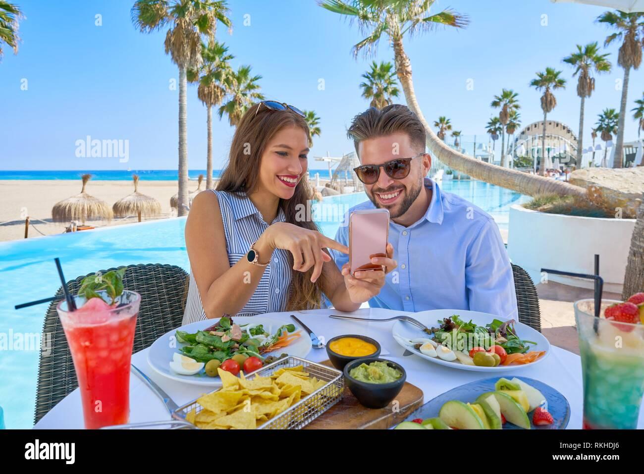 Pareja joven con el smartphone en un restaurante de la piscina. Imagen De Stock