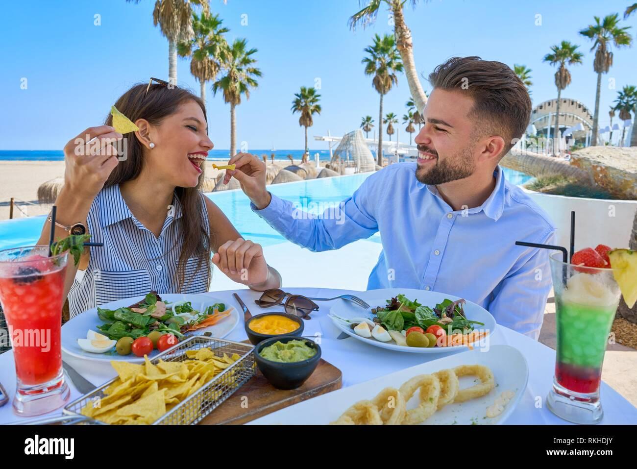 Pareja joven comiendo en un restaurante de la piscina. Imagen De Stock