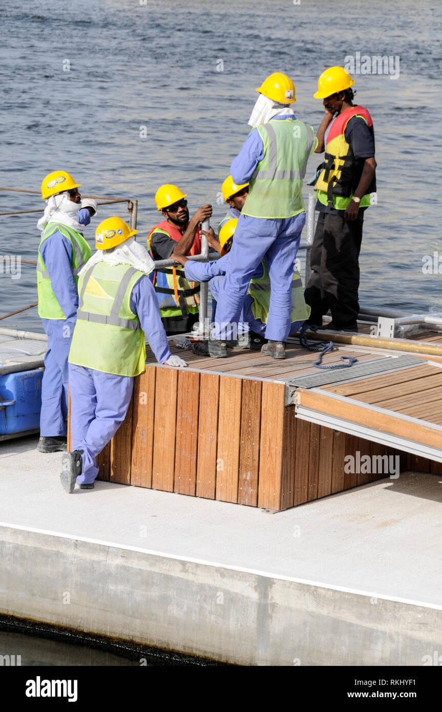 a058d9cf42 Los trabajadores de la construcción de Asia en una plataforma flotante  sobre la cala de Dubai