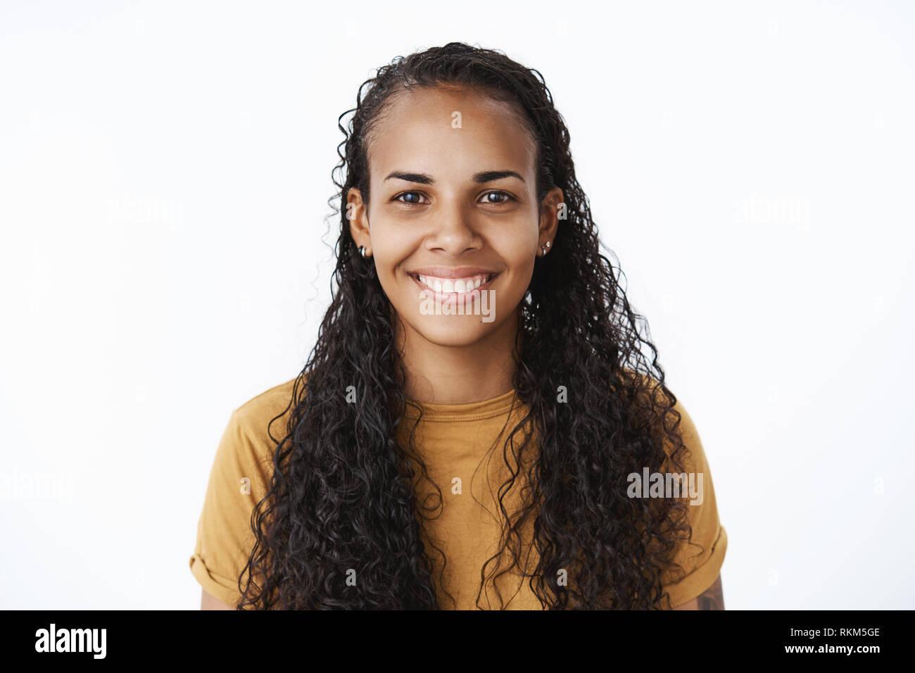 Clsose-up shot de gozosa buena apariencia amable mujer afroamericana con mucho pelo rizado y blanco amplia sonrisa mirando a la cámara y cumplido Imagen De Stock
