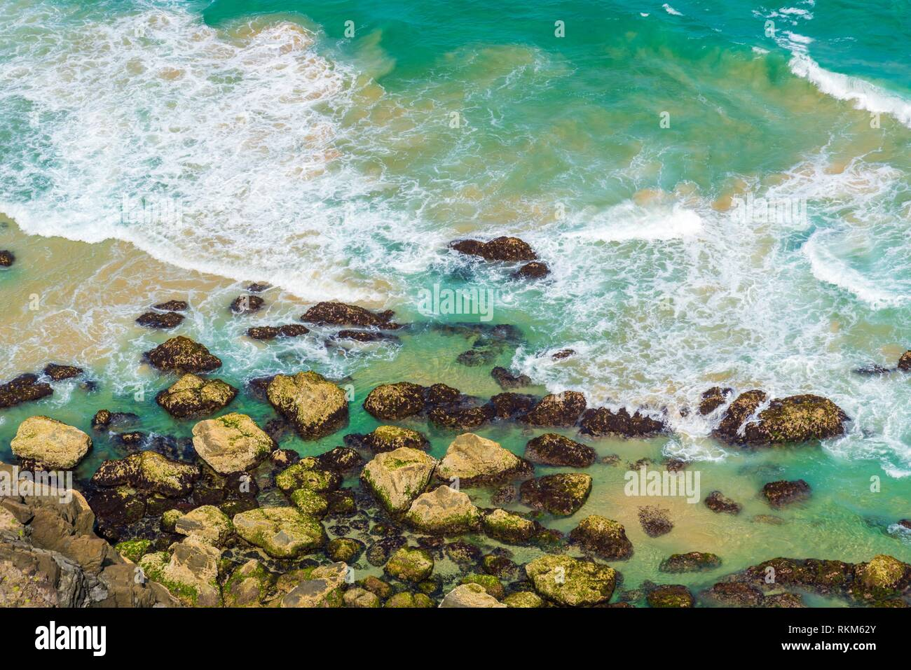 Vista aérea sobre ondas de agua turquesa verde en Byron Bay, Australia. Naturaleza del fondo con las aguas oceánicas y rocas en día soleado. Foto de stock
