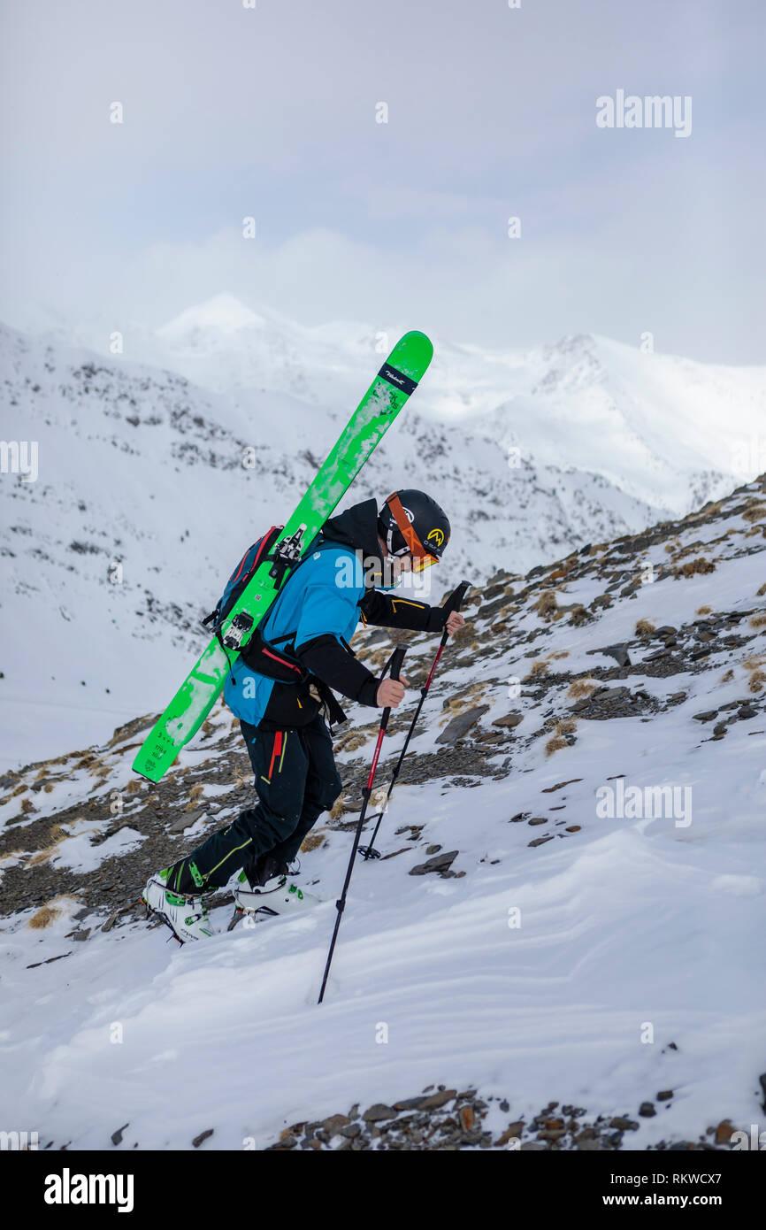 Esquiador trekking a la cima de la capa de polvo en un día. Foto de stock