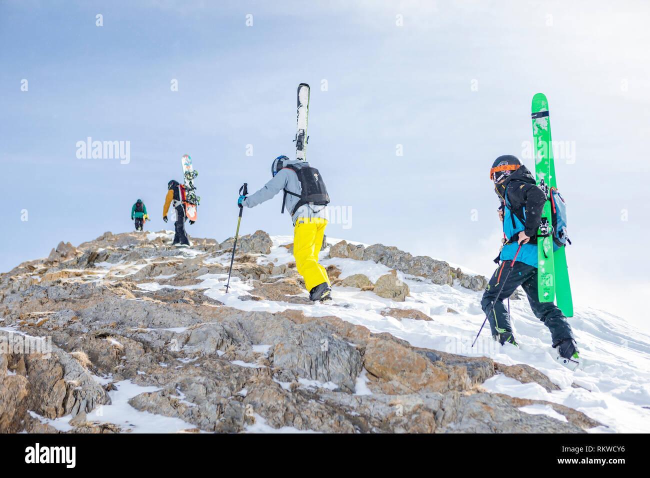 Los esquiadores y snowboarders de nieve trekking a la cima de la capa de polvo en un día. Foto de stock