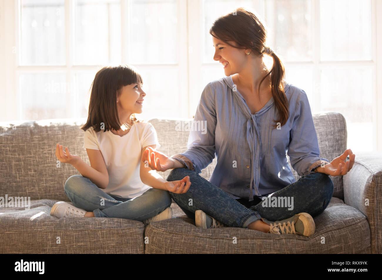 Consciente mamá enseñar yoga niño feliz hija sentado en el sofá Foto de stock