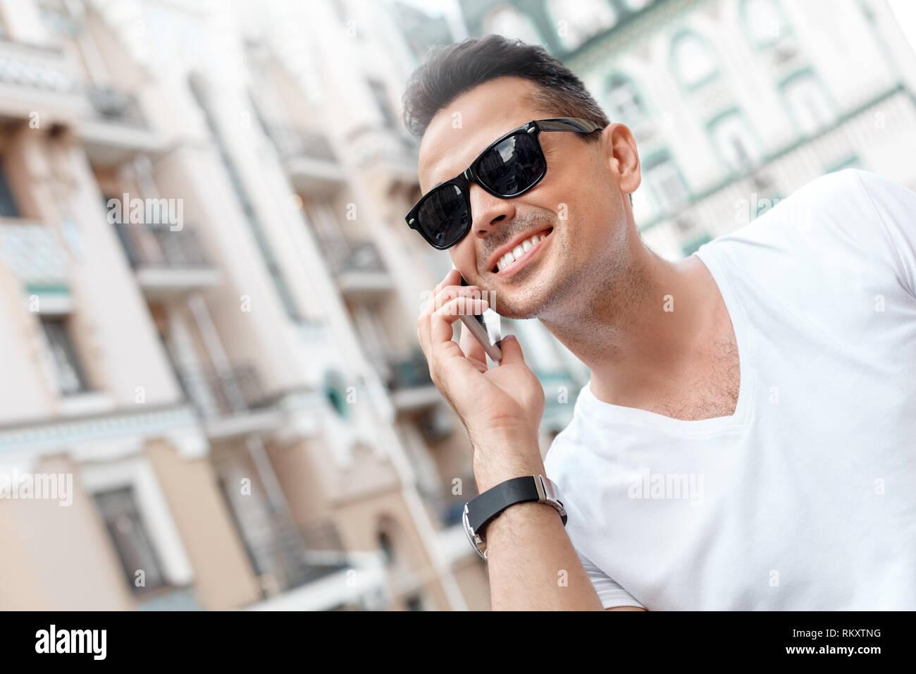 9976413f26 Joven hombre elegante con gafas de sol al aire libre caminando por las  calles de la