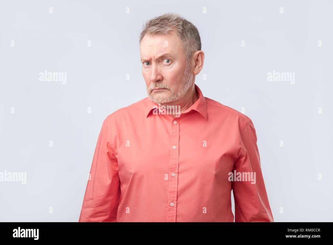 Hombre senior en camiseta roja fruncir el ceño y entrecerrar, mostrando la incredulidad o duda Imagen De Stock