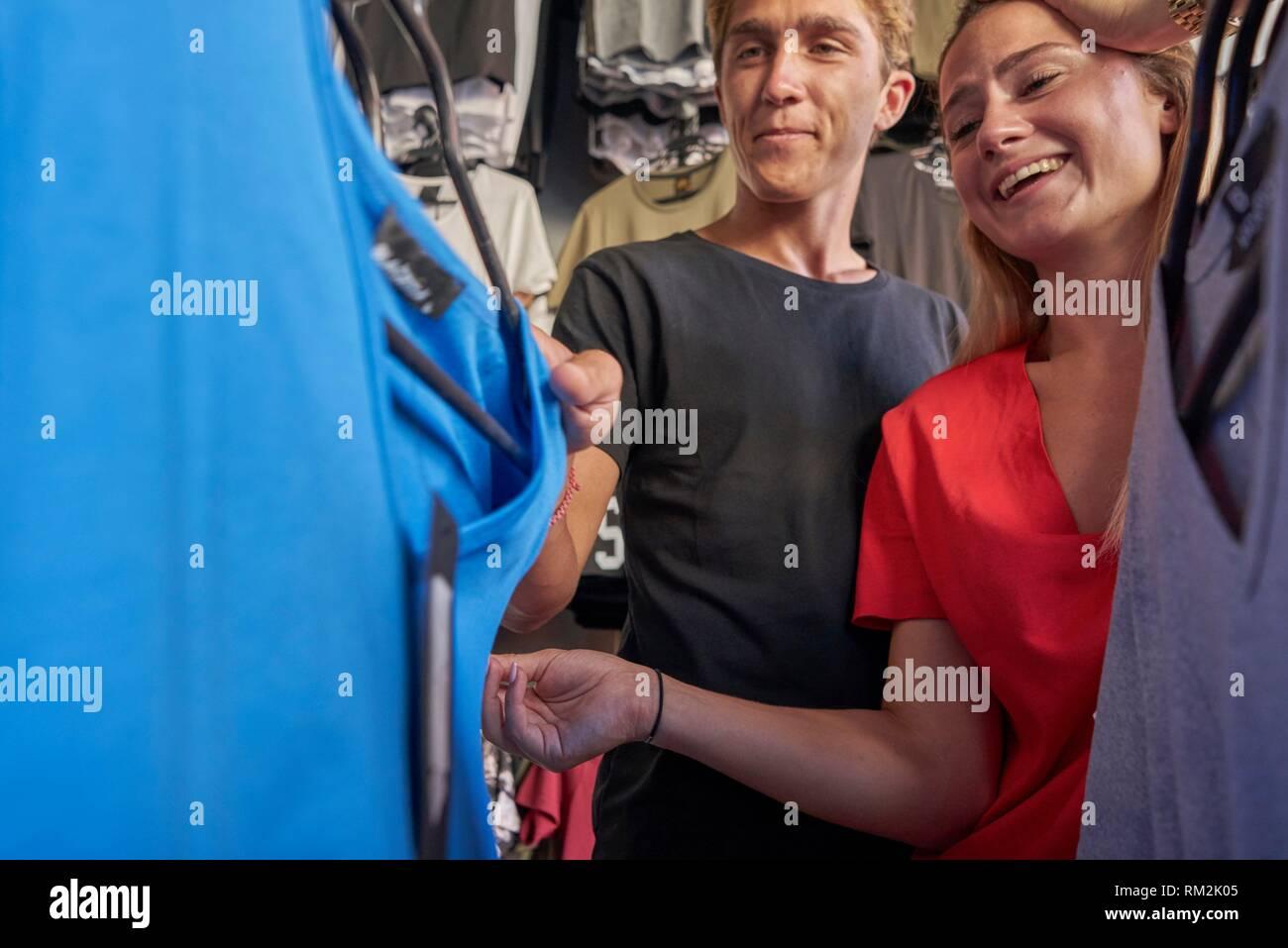 Feliz pareja examinar la ropa en la tienda de ropa. A los 21 años. La etnia neerlandesa Foto de stock