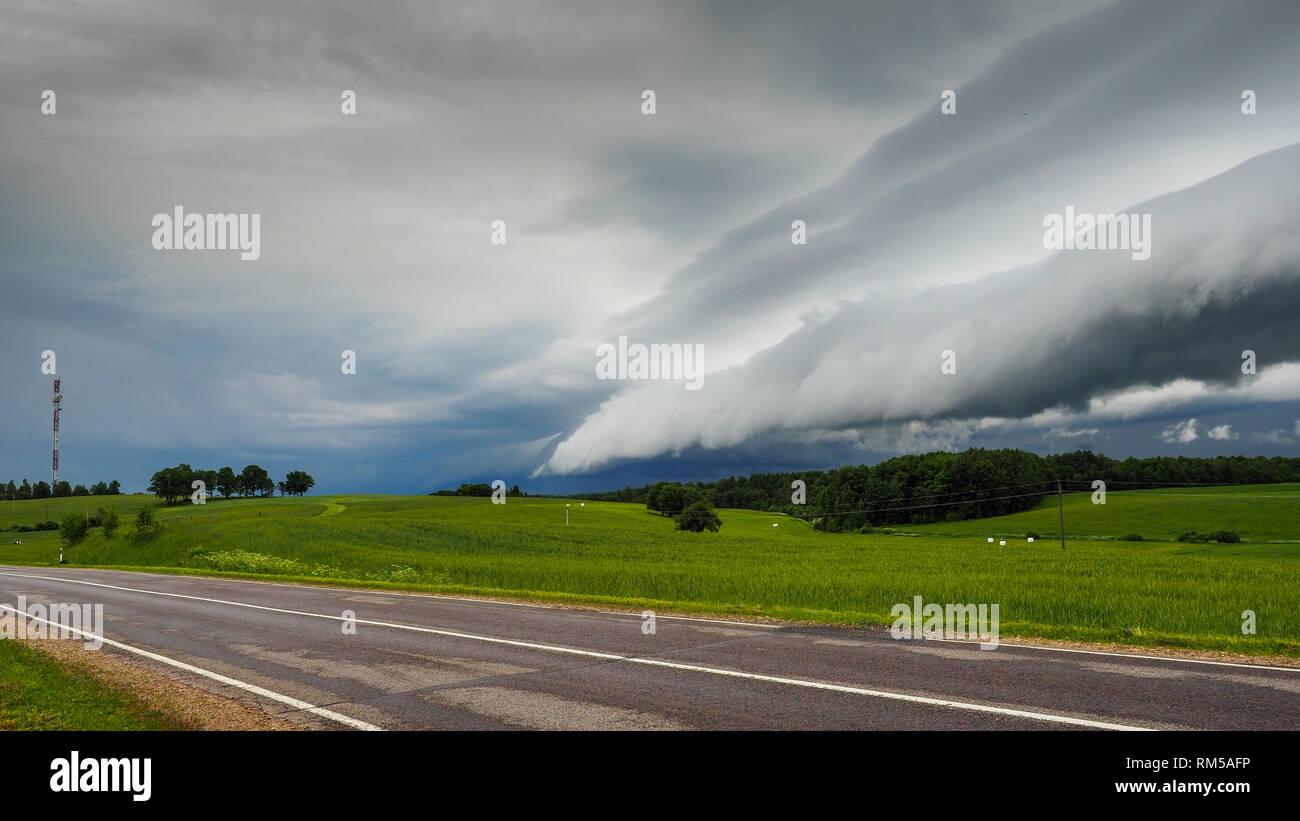 La tormenta o huracán está llegando. Amenazantes nubes de lluvia oscura cubrió el paisaje rústico. Peligroso y sombrío cielo nublado por encima de la tierra. Imagen De Stock