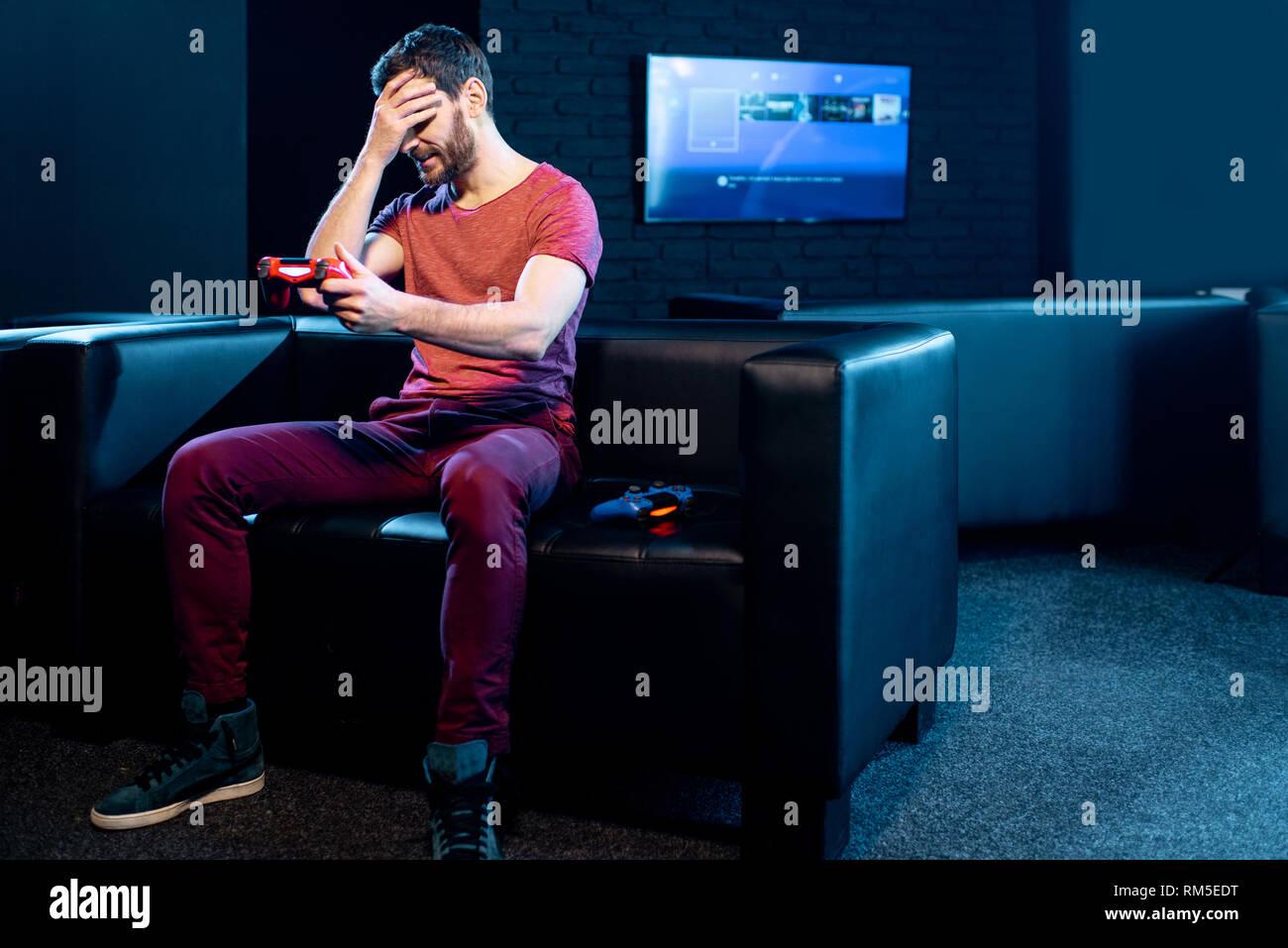 El hombre pierde en video juego sentado en el sofá con la ...