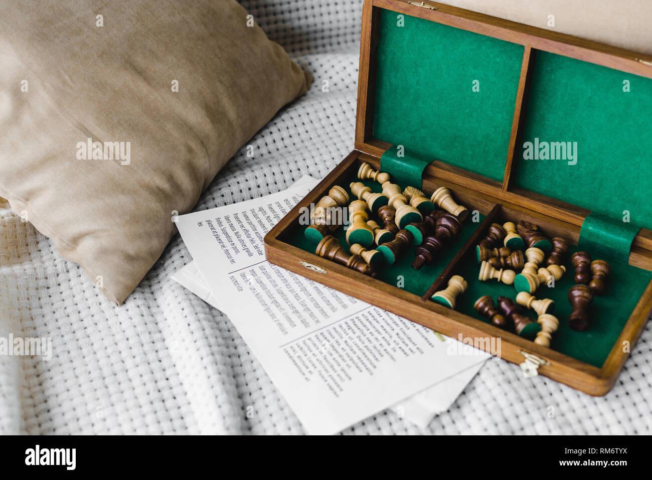 Tablero de ajedrez de madera cerca de periódico en sofá en casa Foto de stock