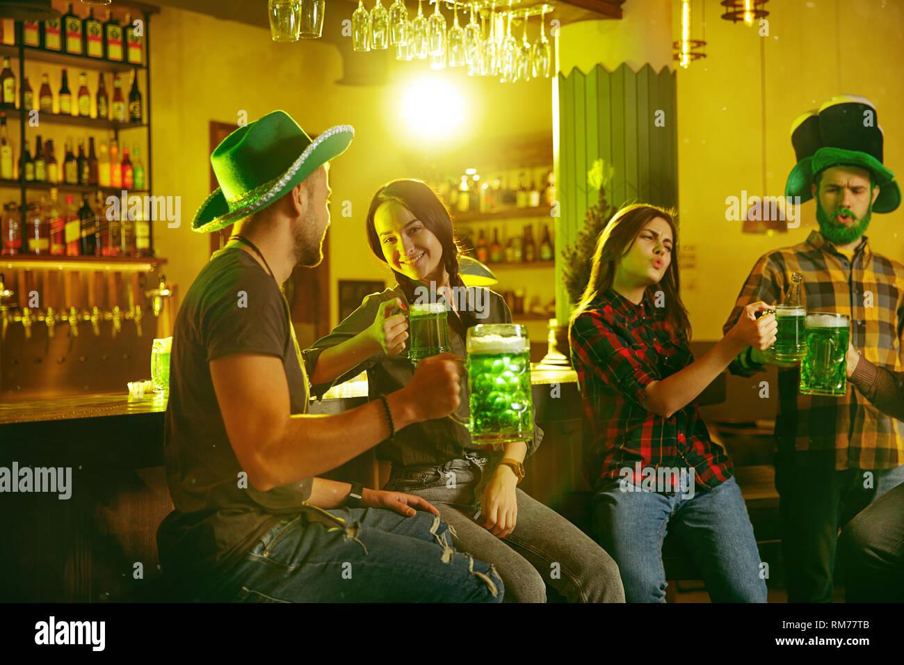 Fiesta del Día de San Patricio. Feliz amigos está de fiesta y bebiendo  cerveza verde d39e6e67235